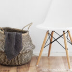 chair on floor and a big basket with cloth sticking out