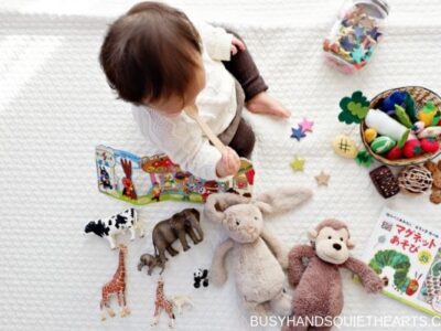 Child on blanket with a lot of toys