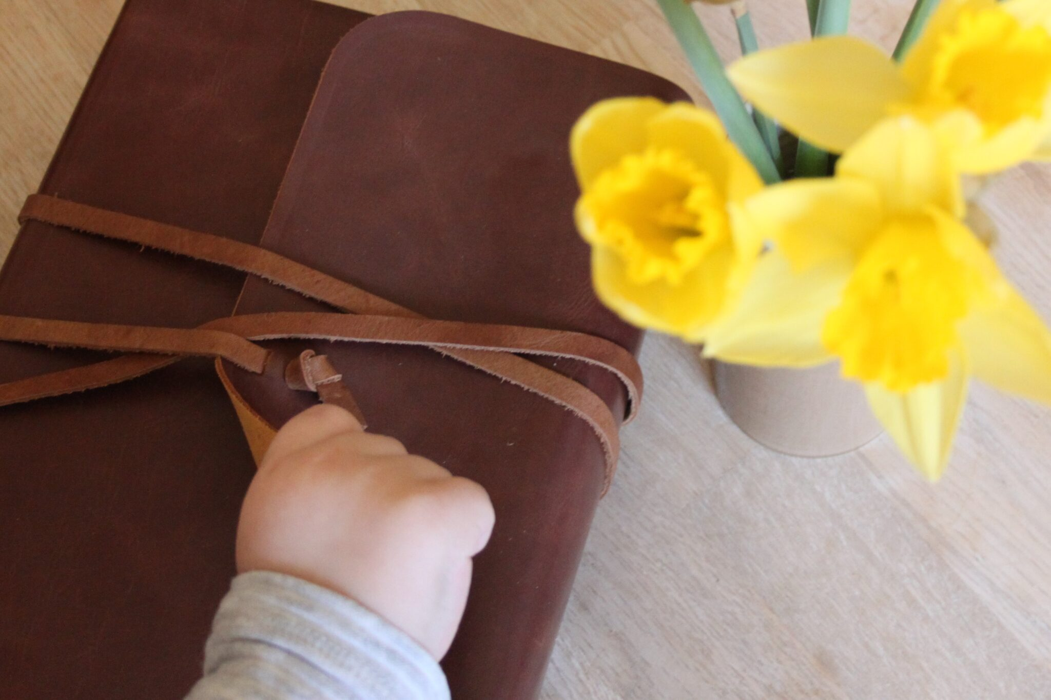 Child's hand on journaling bible and flowers beside it.
