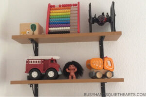Three shelves with toys on them.