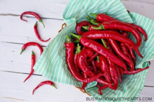 cayenne peppers in a basket lined with cloth and some cayenne peppers on the table.