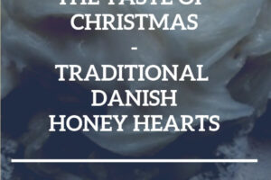 Butcher block counter top with flour and honey directly on it. Text overlay: The taste of Christmas - Traditional Danish Honey Hearts