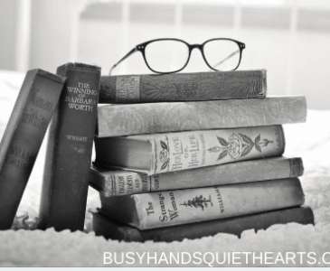 Black and white photo of old books stacked on top of each other with a pair of glasses on top.