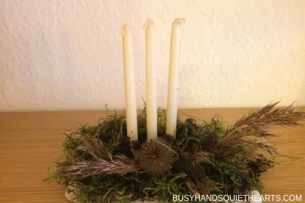 Christmas decoration with three tall candles made by a child.