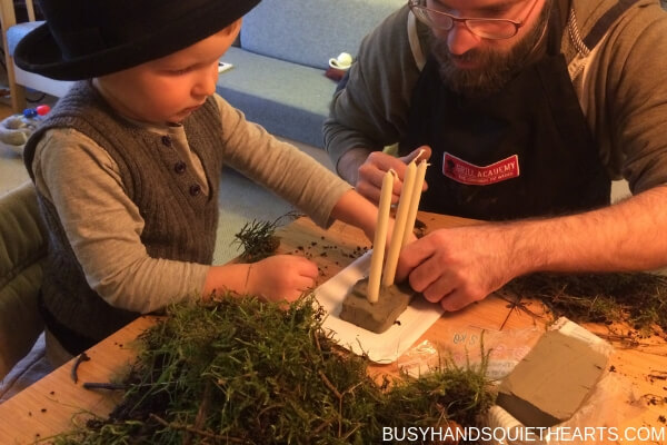 Father and son making a Christmas decoration, placing three candles in clay.
