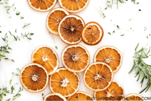 Dehydrated orange slices and herbs on white background