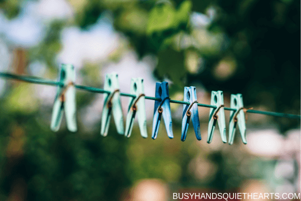 Green and blue clothes pins on a clothes line outside.