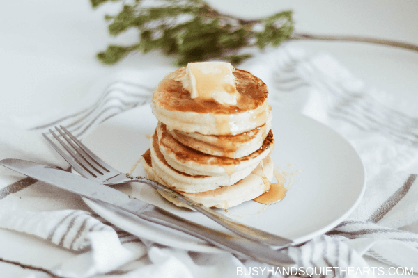 A big blob of butter on a stack of pancakes, with cutlery and herbs in the background.