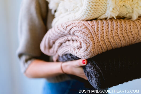 A lady holding a stack of knitwear.