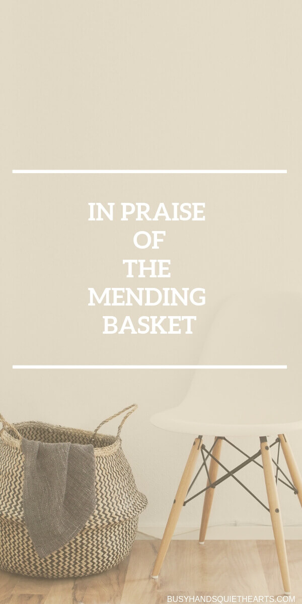 A big basket with clothes sticking out on the floor besides a chair. Text overlay: In praise of the mending basket.