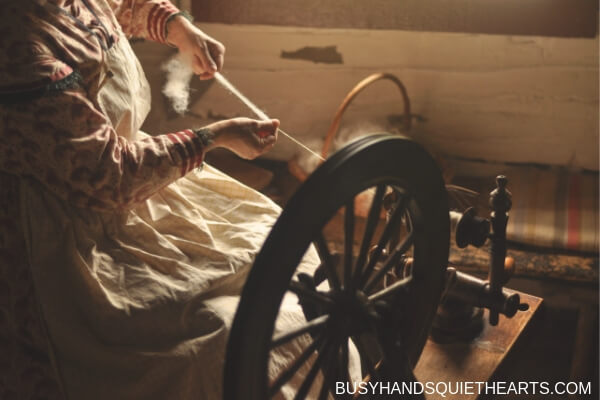 Lady spinning long draw at an antique spinning wheel.