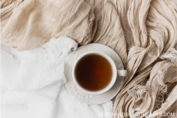 A cup of tea on bed sheets in while and beige