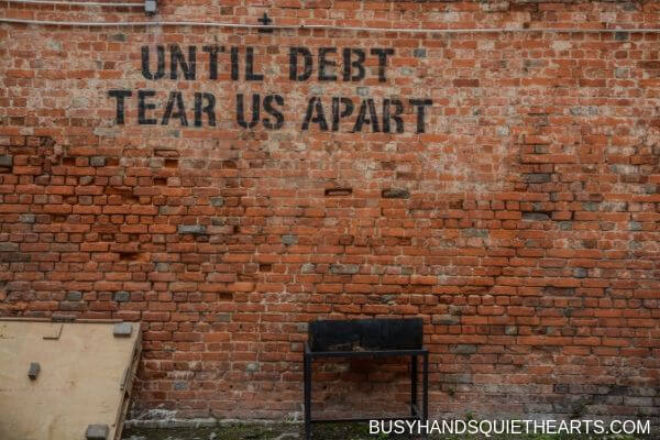 A brick wall with the words: Until debt tear us apart.