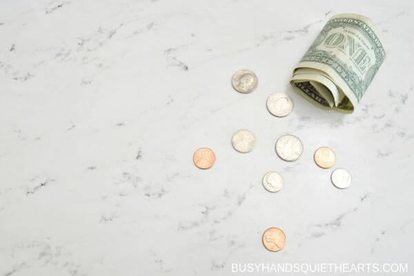 A roll of bills and coins spread on a countertop.