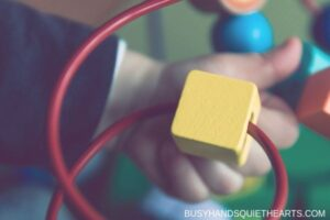 Child's hand holding yellow square on a block toy