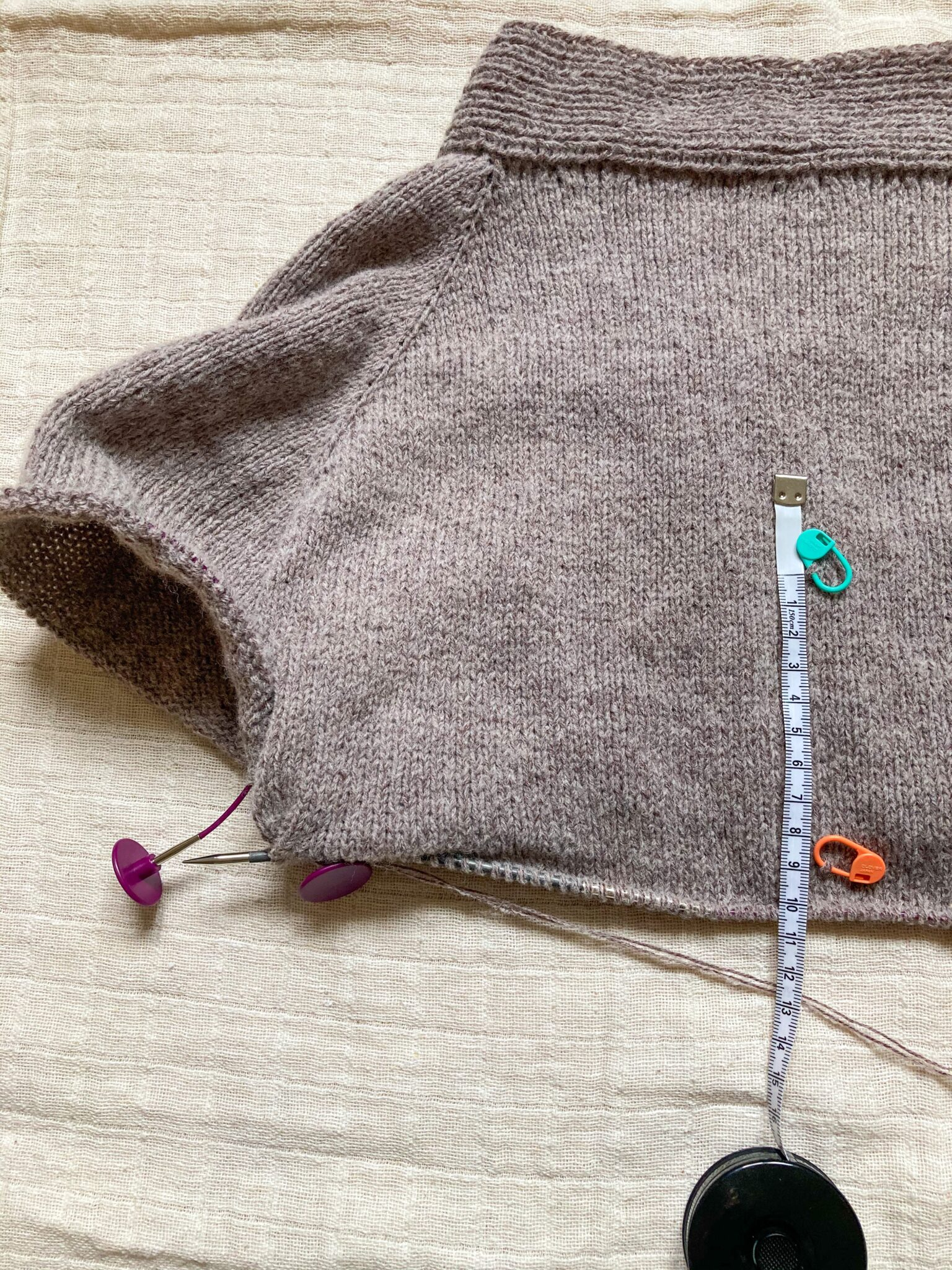 No Frills cardigan with measuring tape showing progress. 10 cm knit from stitch marker.