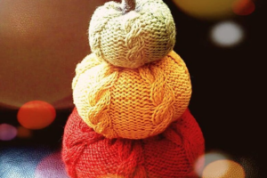 Three knitted pumpkins stacked in different sizes