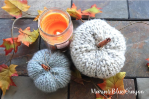 two knitted pumpkins with a lit candle