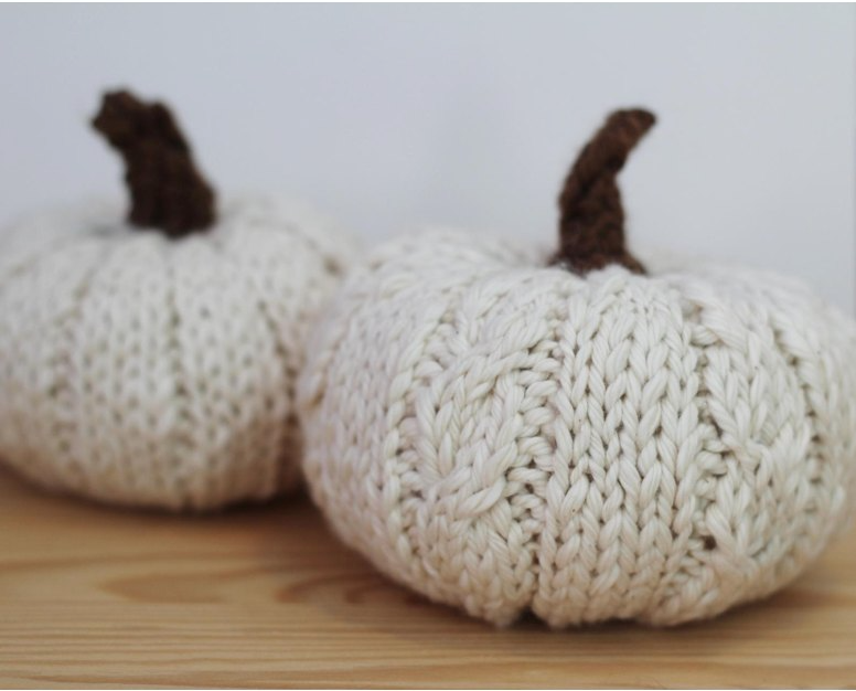 Two knitted white pumpkins with cables