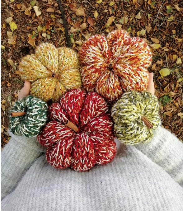 five knitted pumpkins held by two hands
