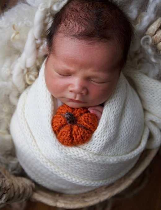 Baby in a wrap with a knitted pumpkin