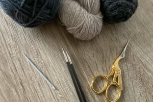 essential knitting tools, yarn, knitting needles, darning needle and scissor